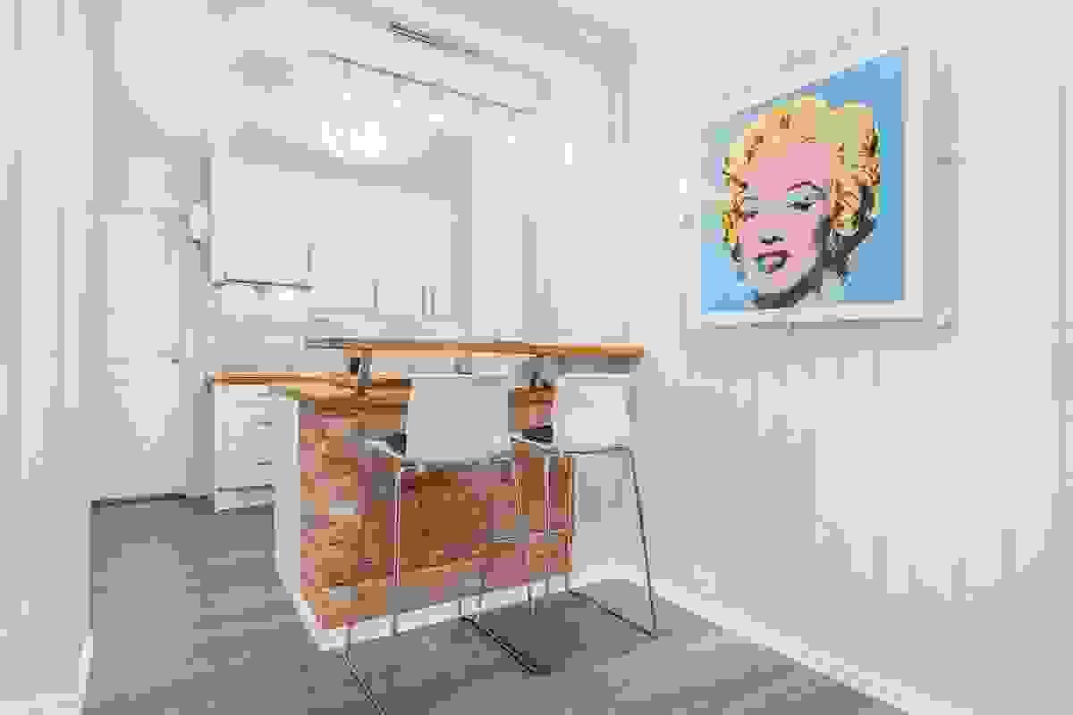 Den integrerte kjøkkenøyen med forhøyet anretningsbenk over benkeplaten sørger for at du kan benytte denne som en kombinert spiseplass