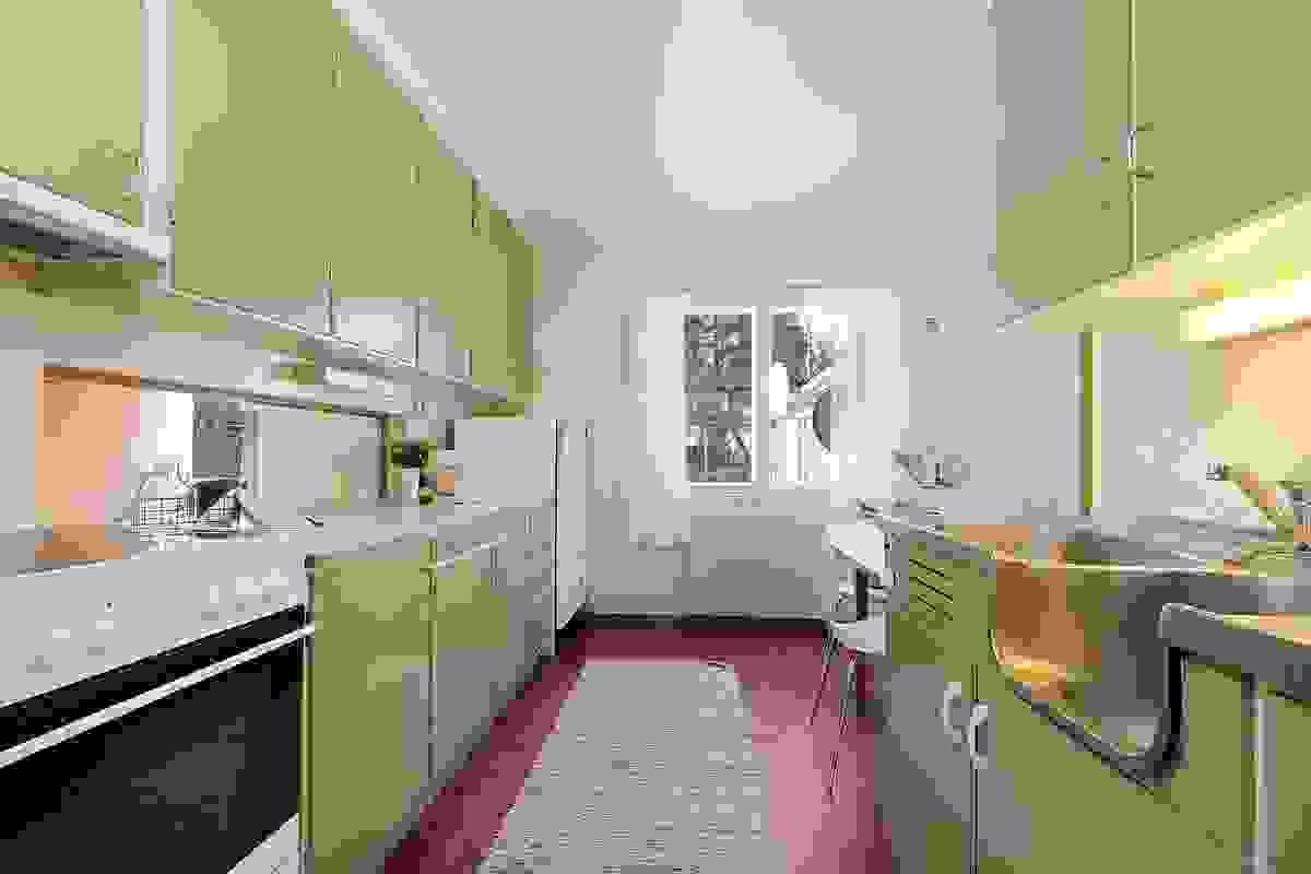 Plassbygd kjøkkeninnredning fra byggeår med overskaper til himling og serveringsluke til stue/spiestue