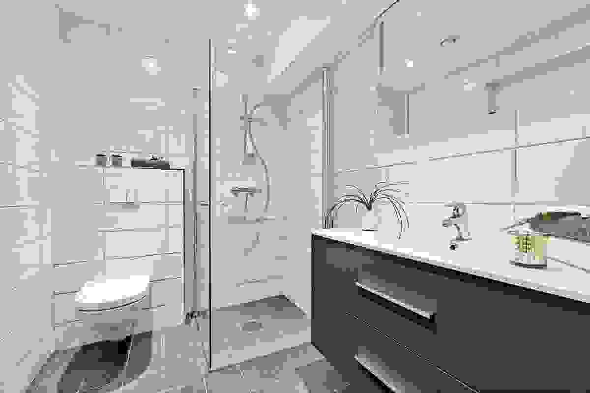 Bad 1. etasje inneholder dusjvegger, heldekkende servant med innredning og  og vegghengt wc