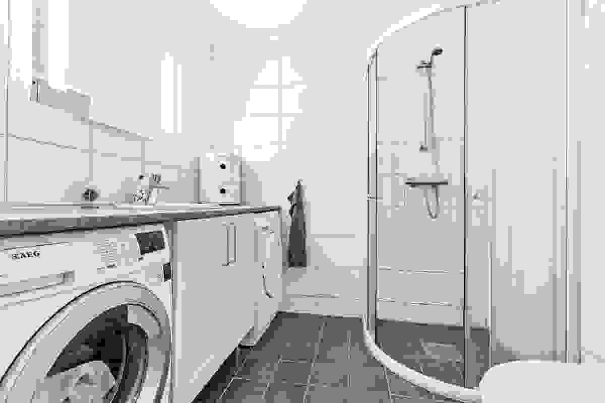 Badet med inngang fra entre/hall er innredet med veggmontert toalett med skjult sisterne og dushjørne m/glidedører av herdet glass