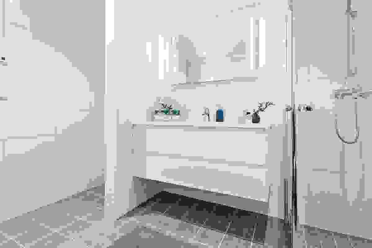 Begge baderommene er innredet med dushjørne m/dører av herdet glass hvor gulvet har mindre fliser enn øvrig gulvflate