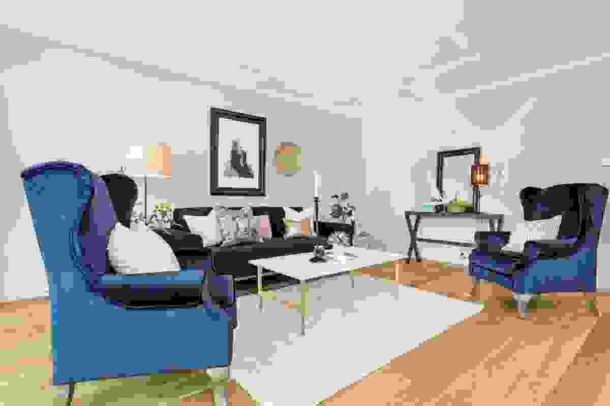 """Det er godt med veggplass å møblere mot, stuens vinkelløsning gjør at rommets naturlige plassering av """"salong-/sittegruppe"""" er godt skjermet fra kjøkkendelen."""