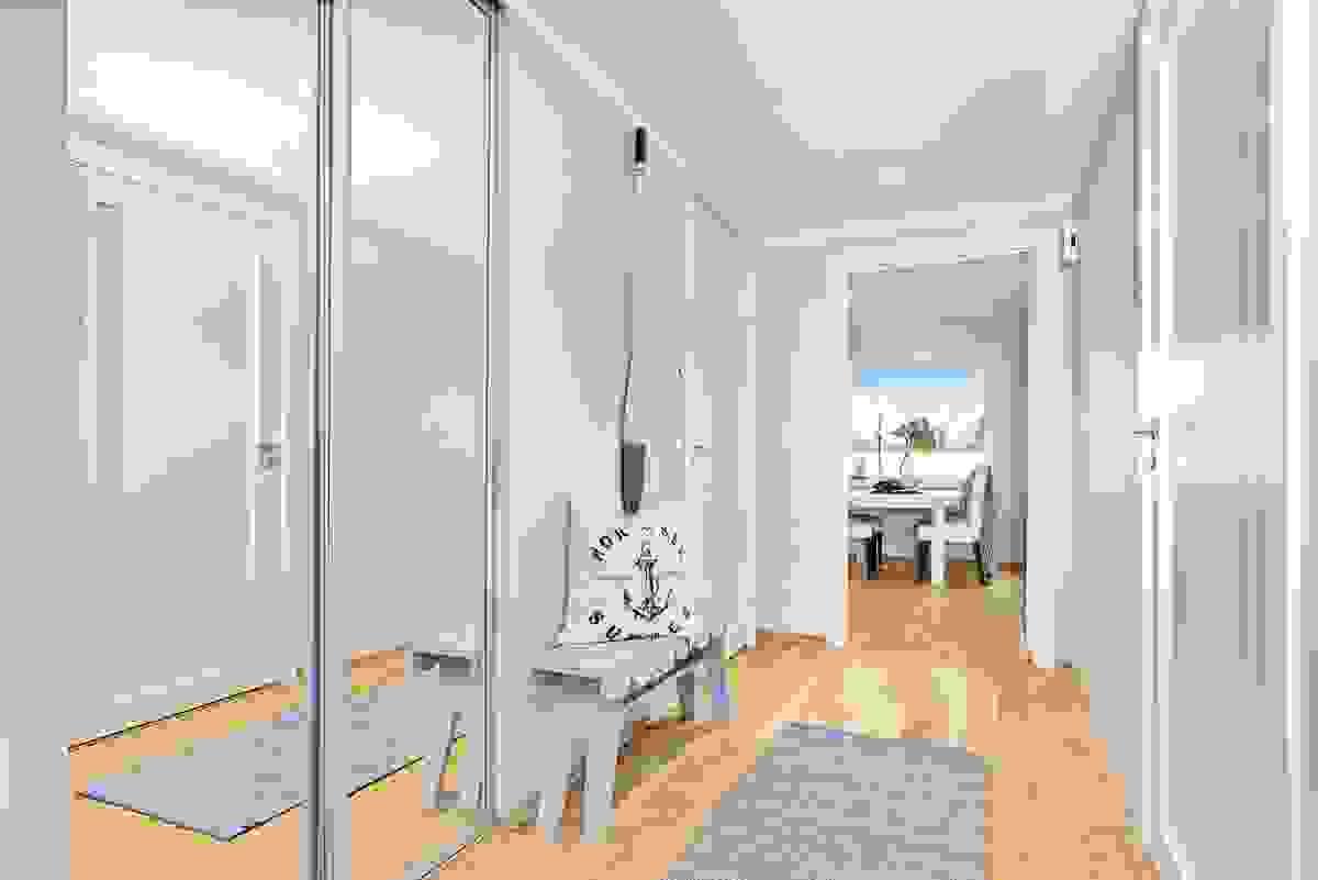 Den brede og romslige entreèn har en praktisk, innfelt 2-dørs skyvedørsgarderobe fra Elfa med dører av speil