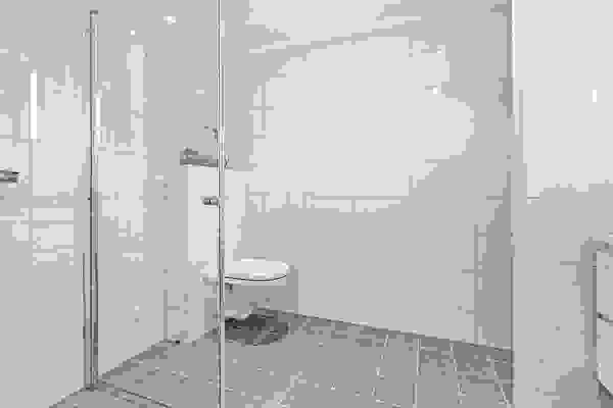Baderommet har flislagte vegger og flislagte gulv med elektrisk gulvvarme.
