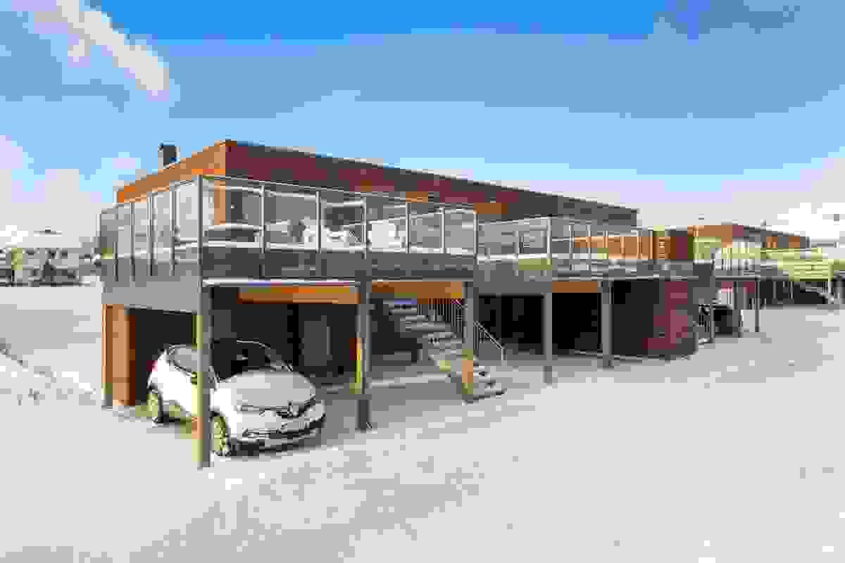 Leiligheten har egen carport ved inngangspartiet på østsiden av bygget