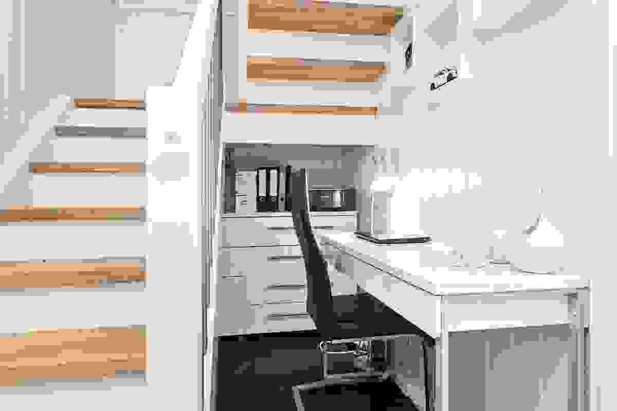 Ved trappen er en smart kontor- og oppbevaringsplass