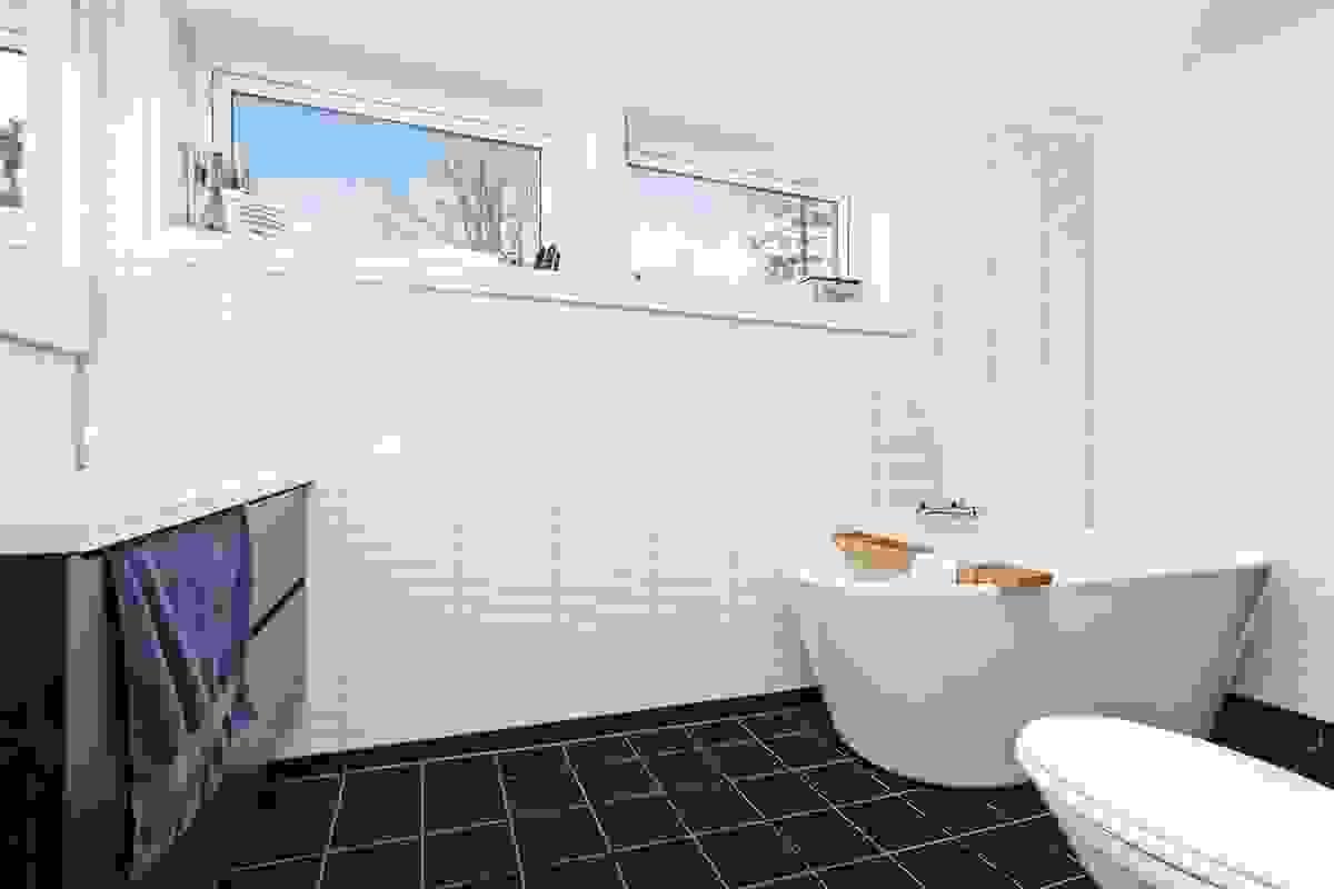 Lekkert bad i 2. etasje med servant i innredning, stilig badekar, dusjhjørne og vegghengt wc