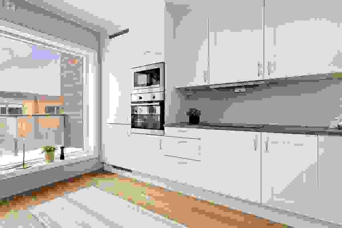 Belysning mellom over-/undersekap, og områdene uten overskap gir plass for veggpryd eller praktiske hyller dersom ønskelig.