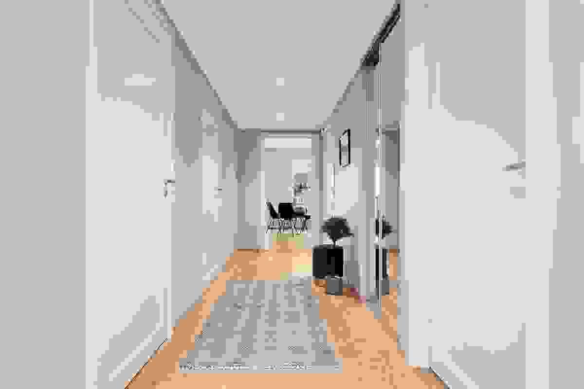 Den brede og romslige entreèn har en praktisk, innfelt 2-dørs skyvedørsgarderobe fra Elfa med dører av speil. Rommet er på drøye 10 m², og det er plass til ytterligere plass for kommoder, skoskap eller lignende