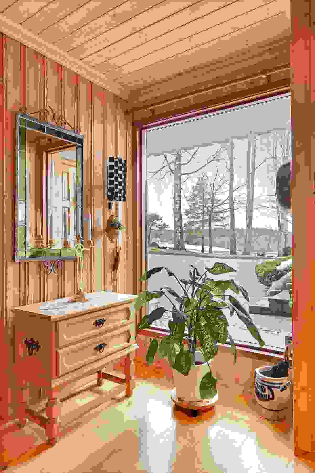 Hall med stort vindu som slipper inn naturlig lys
