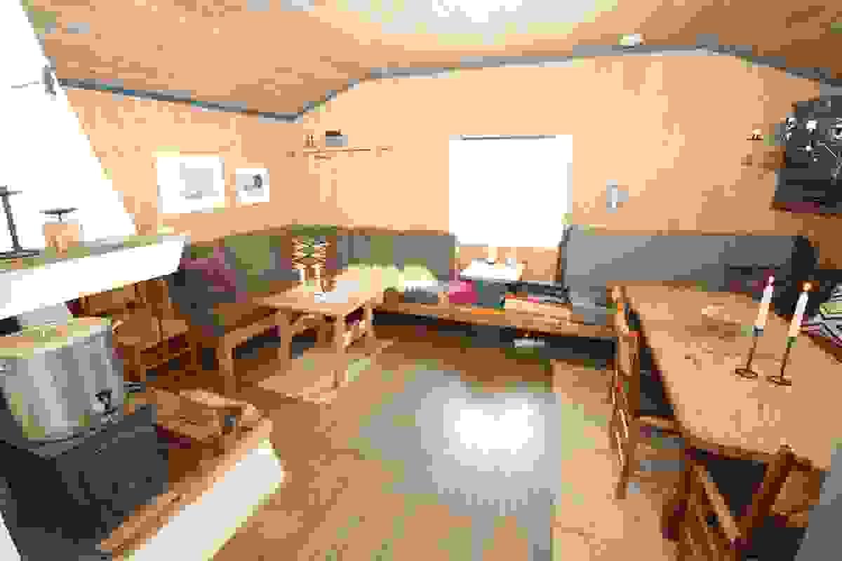 Stue med plassbygd sofa og avsatt sted for spisebord