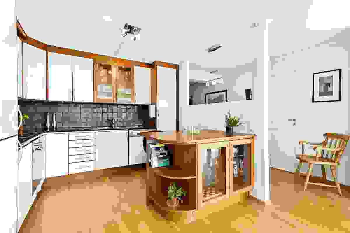 Kjøkkenet er påkostet med blant annet hvitevarer av høy kvalitet og en praktisk kjøkkenøy med anretnings-/spisebord og underskap med glassdører