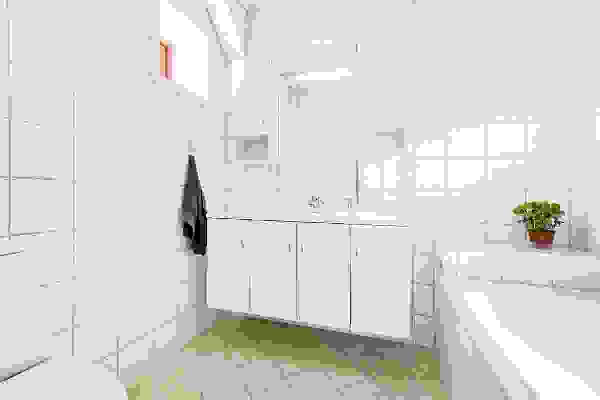 Baderom/wc 1, som ligger i kombinasjon med hovedsoverommet, har flislagt gulv (varmekabler), flislagte vegger og hvitmalt himling