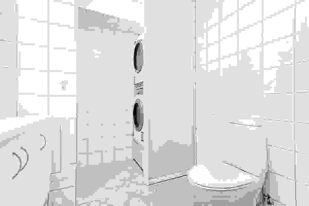 """Legg merke til den elegante og praktiske løsning med skjult """"vaskeromsnisje"""" innenfor rommet med skyvedører av hvit-/frostet glass"""