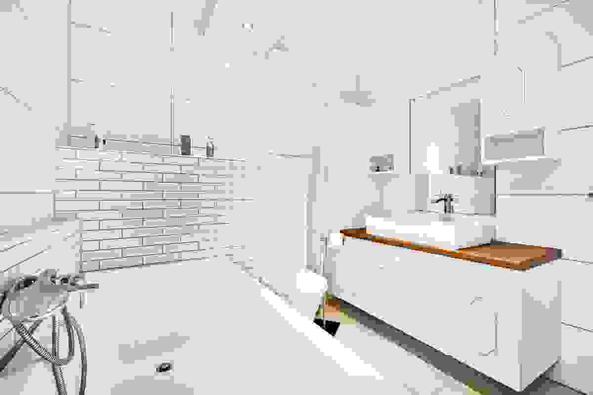 Bad inneholder badekar med dusjmulighet, vegghengt WC og baderomsinnredning med servant