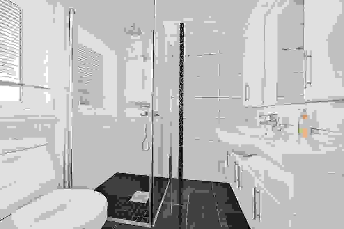 Baderom med baderomsinnredning med heldekkende servant, dusjvegger og WC