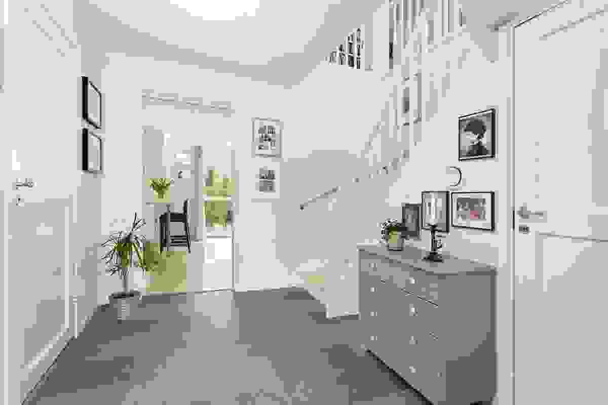 Innenfor en åpen og romslig hall med fliser og varmekabler i gulv
