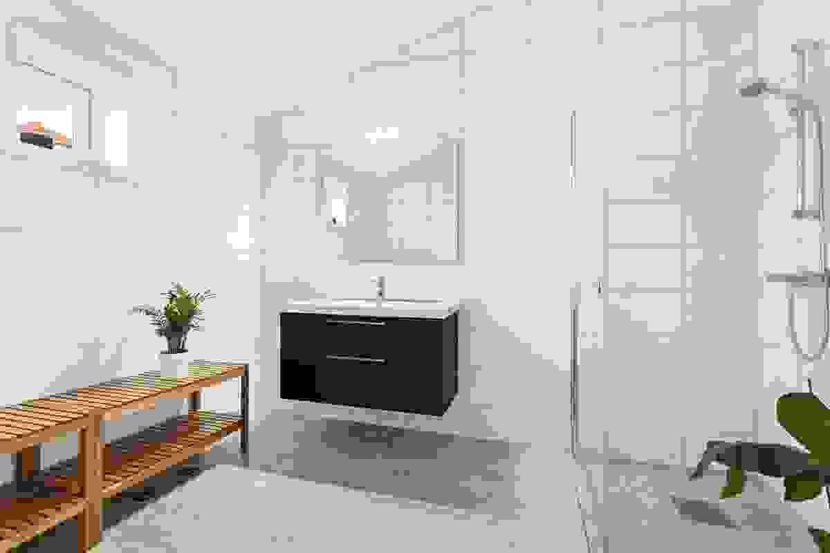 Badet er delikat innredet med fliser på gulv og vegger, og varmekabler