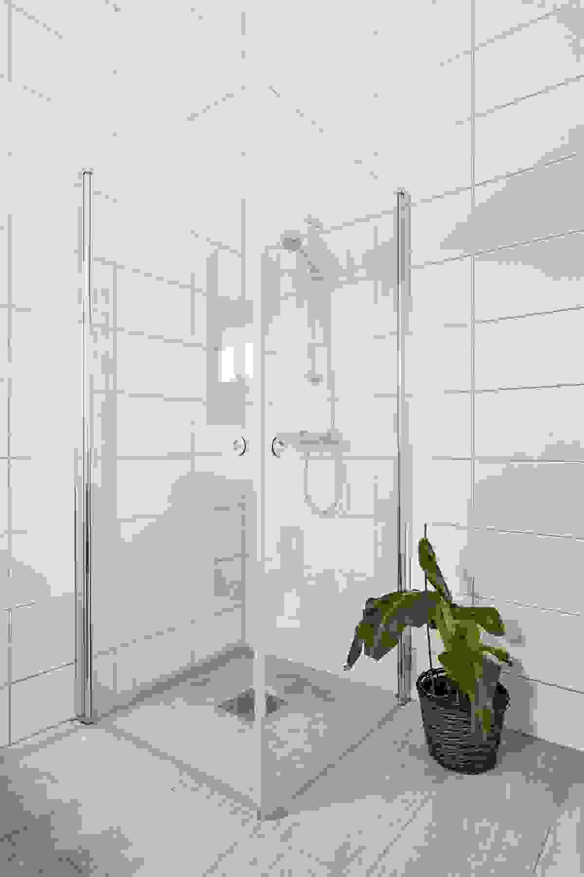 Rommet inneholder dusjhjørne, servant i innredning og vegghengt wc