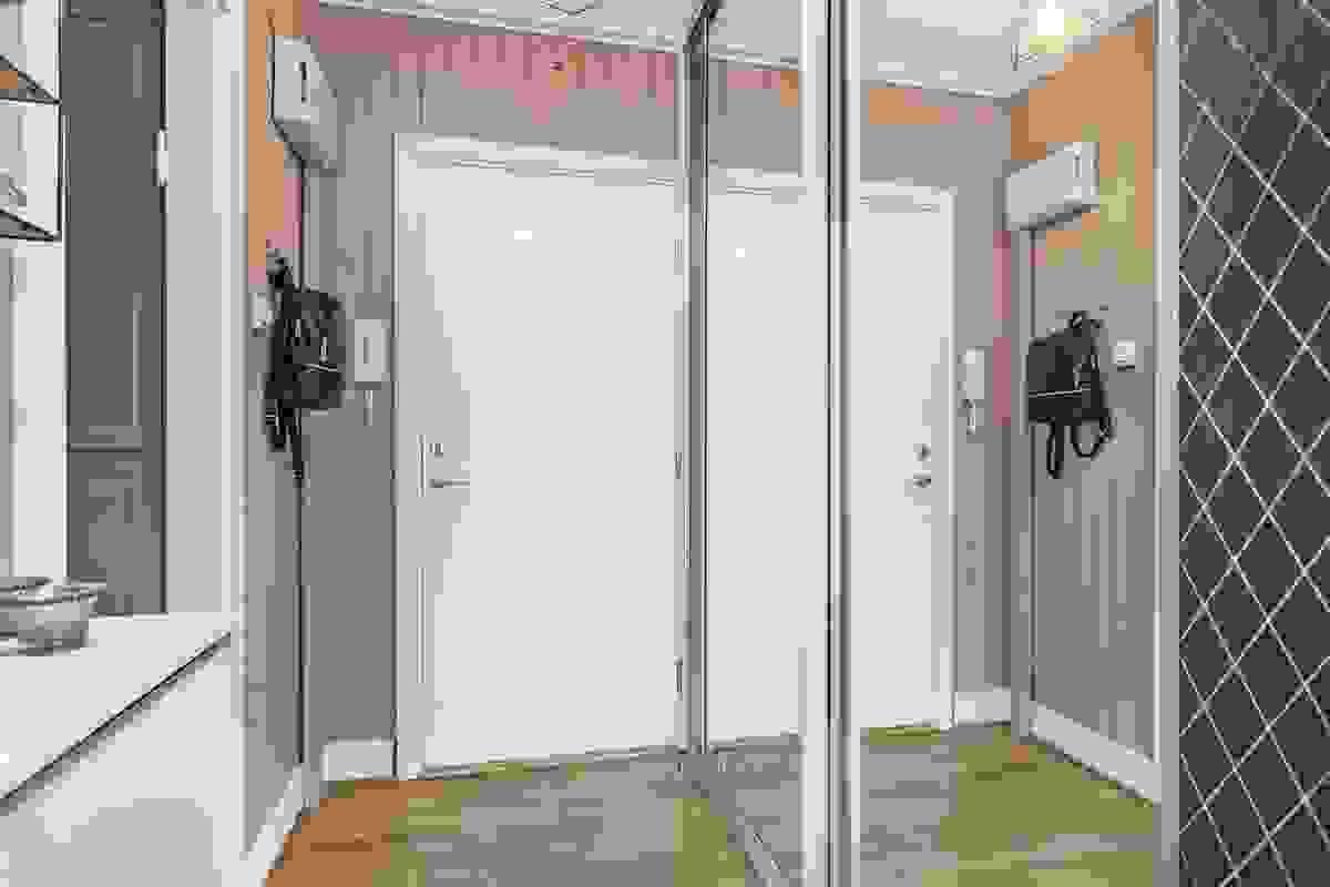 Entréen i leiligheten er nydelig innredet med malt panel og skyvedørsgarderobe med speil