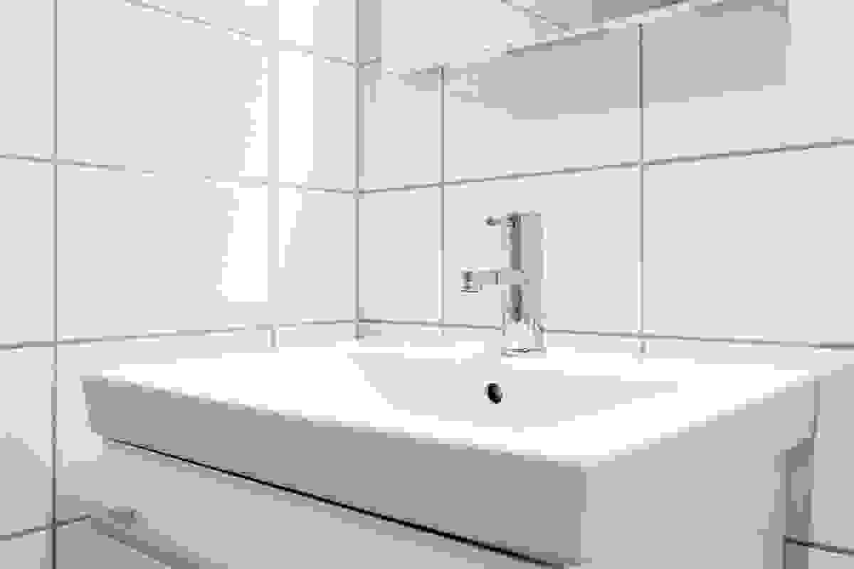 Badet er pent innredet med gråtonede fliser på gulv og matchende fliser på vegger. Varmekabler i gulvet gir deilig temperatur året rundt.