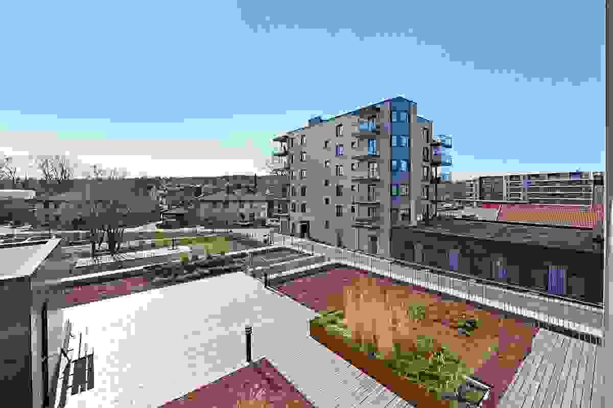 Utsyn fra balkong over fellesområde som er parkmessig utført