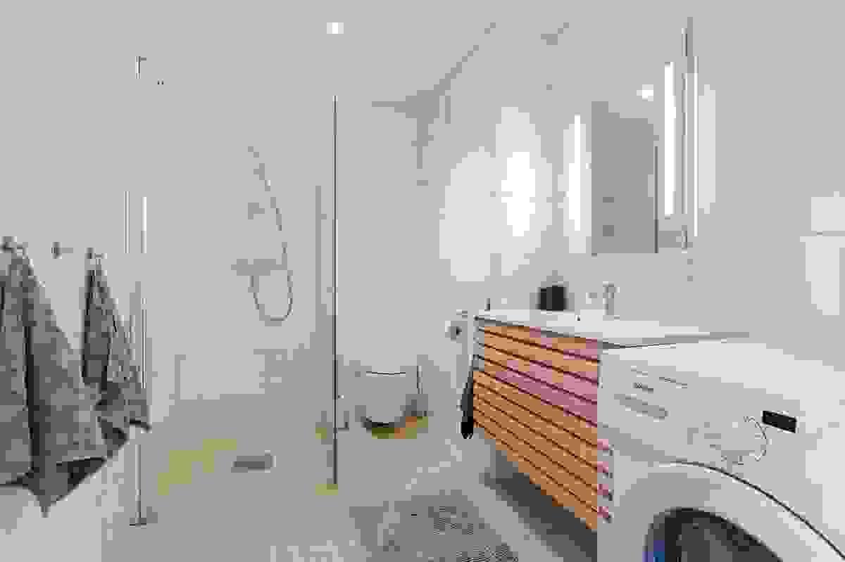 Badet inneholder vegghengt WC, baderomsinnredning, dusjvegger samt opplegg for vaskemaskin og tørketrommel