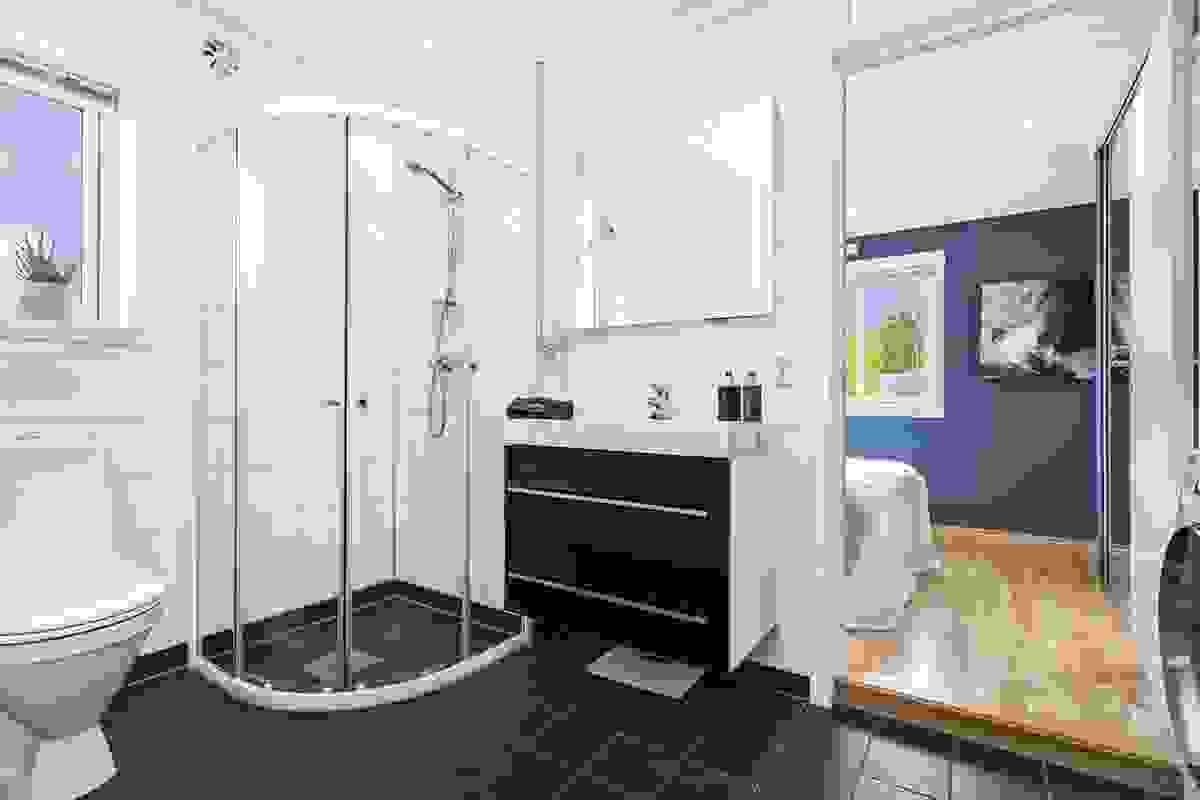 Baderommet er delikat innredet med mørkegrå fliser på gulv og matchende, lyse fliser på vegger. Gulvvarme og avtrekk styres fra digitalt kontrollpanel.