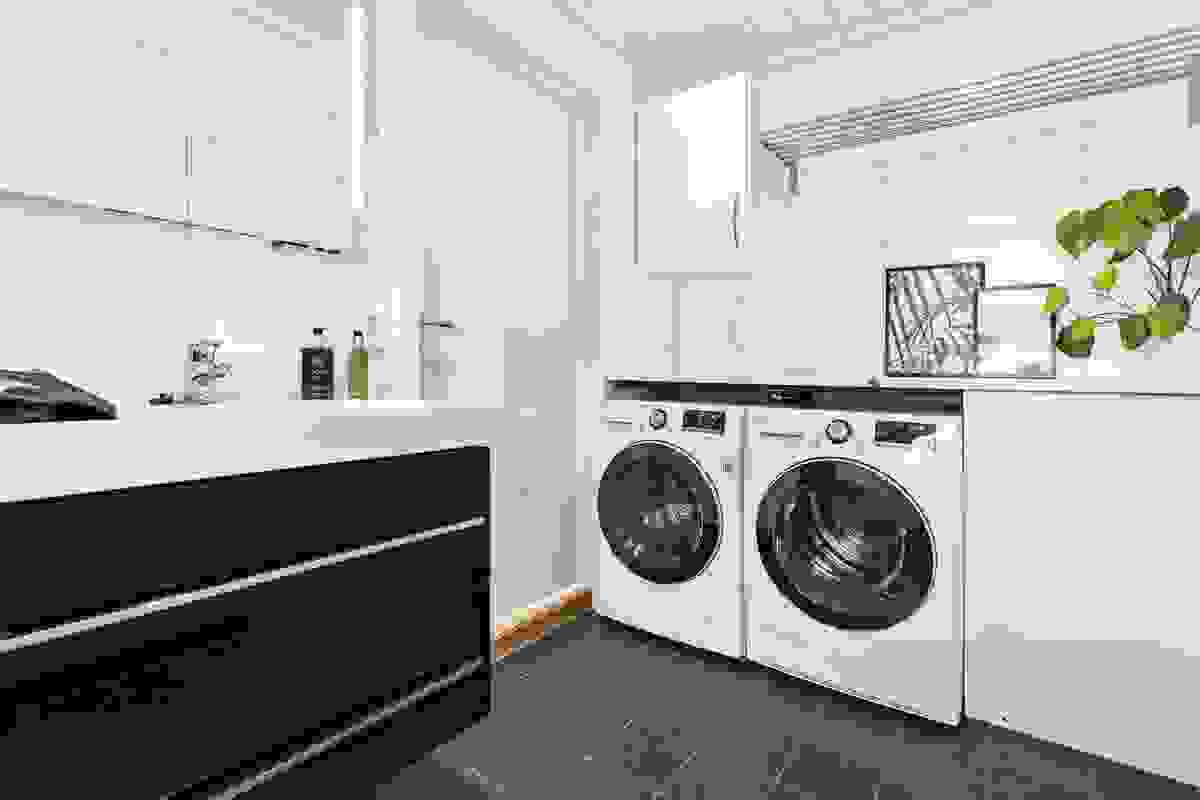 lott løsning med opplegg for vaskemaskin og tørketrommel i nisje under arbeidsbenk. Det er montert hylle og overskap for praktisk oppbevaring
