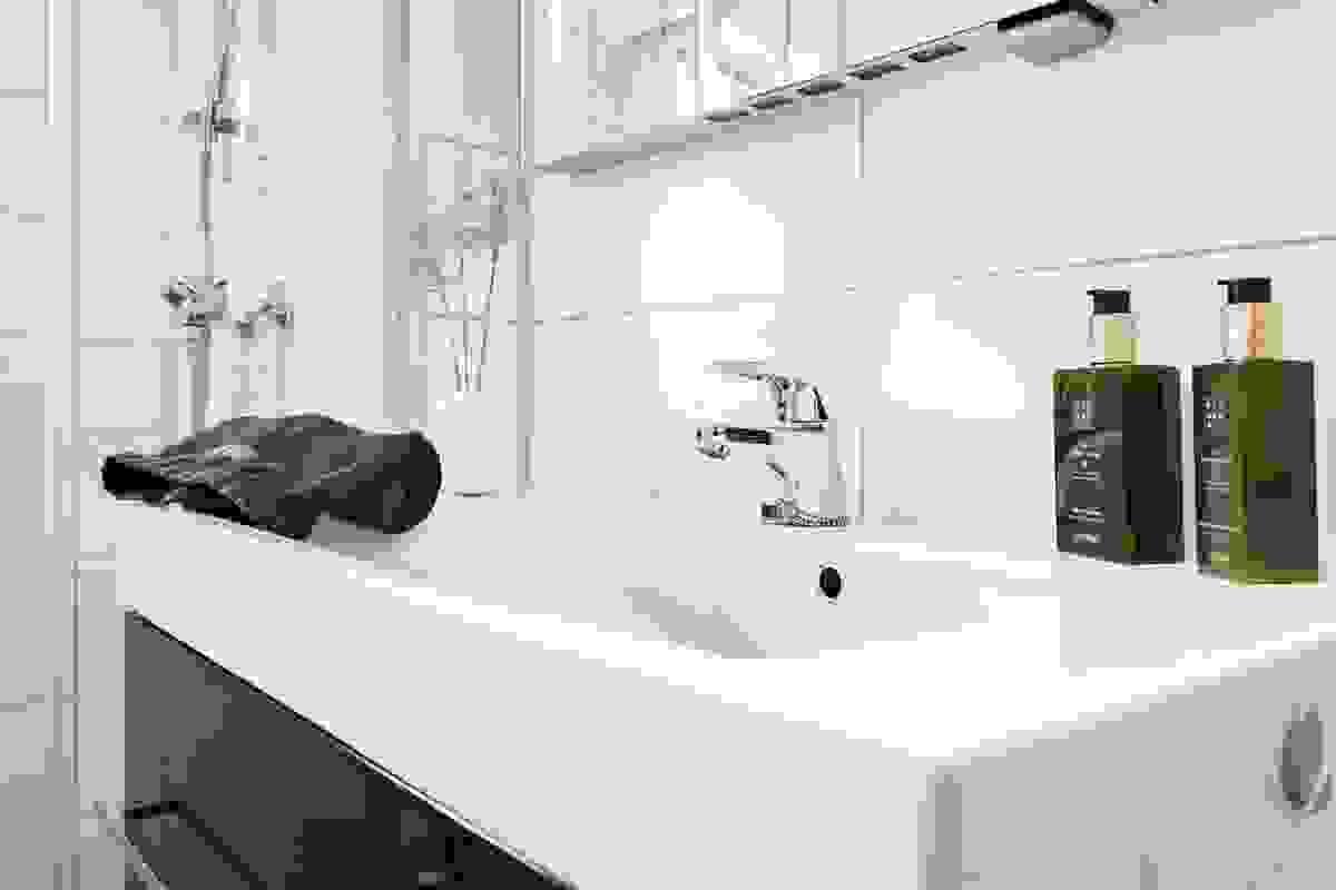 Innredningen består av heldekkende servant nedfelt i sort skuffeseksjon og speil med integrert belysning. Videre er det sokkeltoalett og dusjnisje med skyvedører i glass.