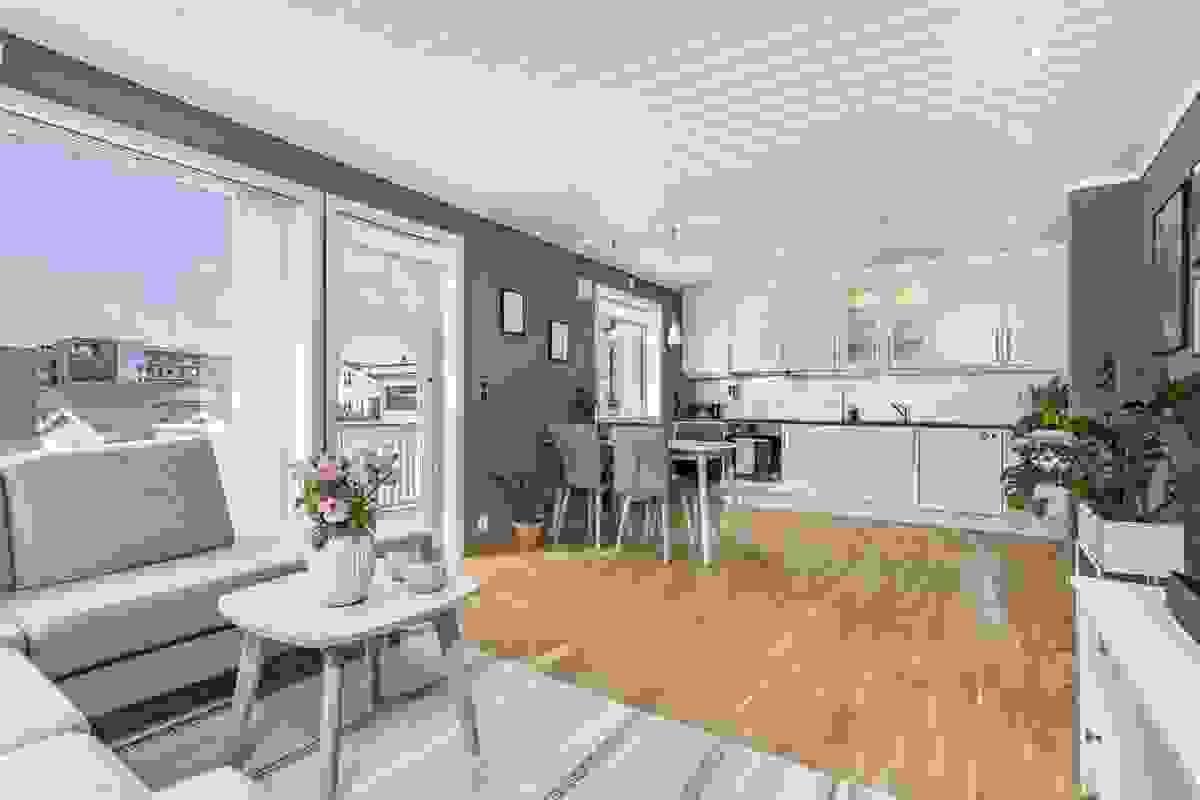 Lys og romslig stue i åpen løsning til kjøkkenet.