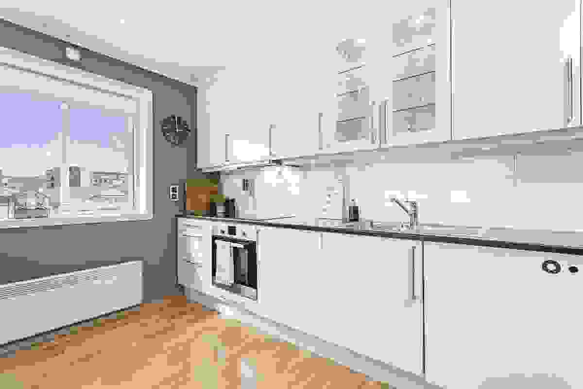 Den moderne og delikate innredningen har hvite, slette fronter, vitrineskap, laminat benkeplate med nedfelt vaskekum og flisplater på vegg mellom benk og overskap