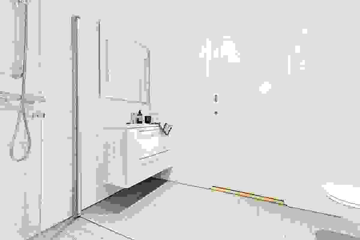Veggene har tidsriktige, rektangulære hvite veggfliser mens det på gulvet er valgt en gråtonet farge for å skape en matchende kontrast