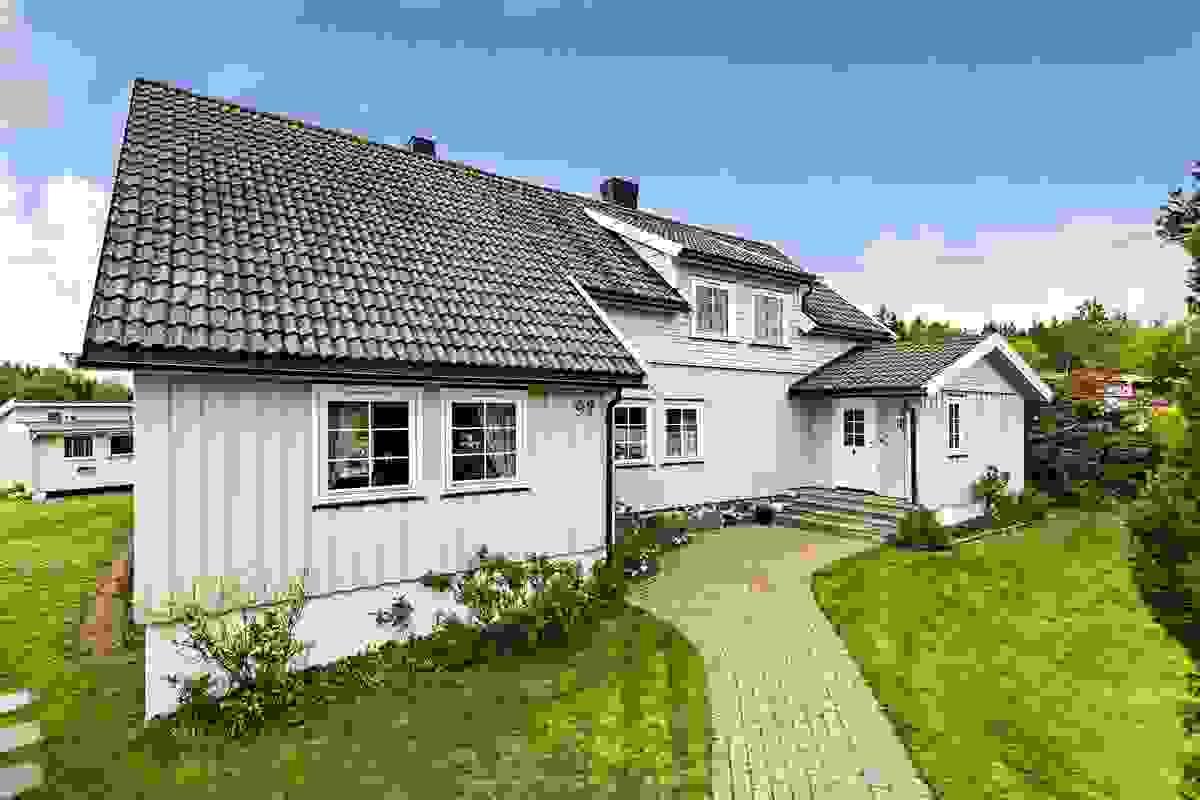 Fremsiden av huset med steinlagt gangareal frem til hovedinngangen