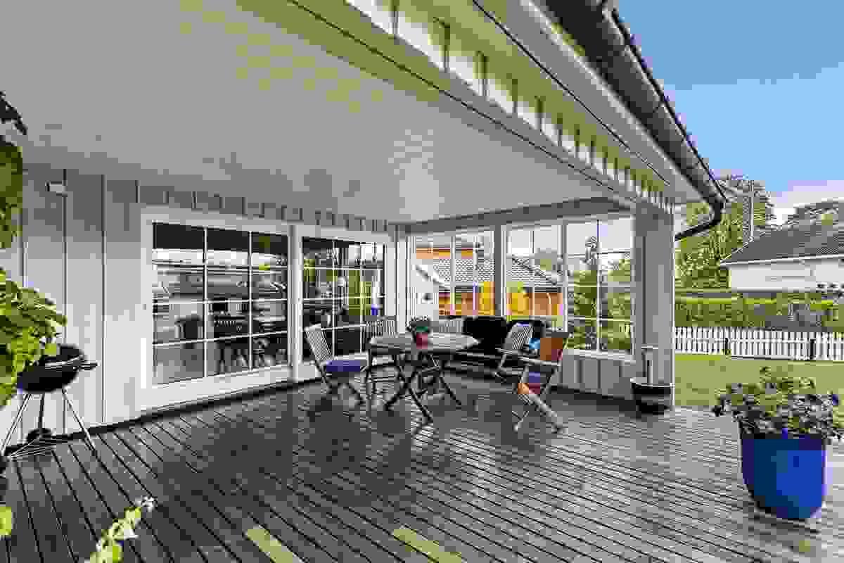 Inn-/overbygget terrasse som er sammenføyet med nedtrappet terrasse i hagen