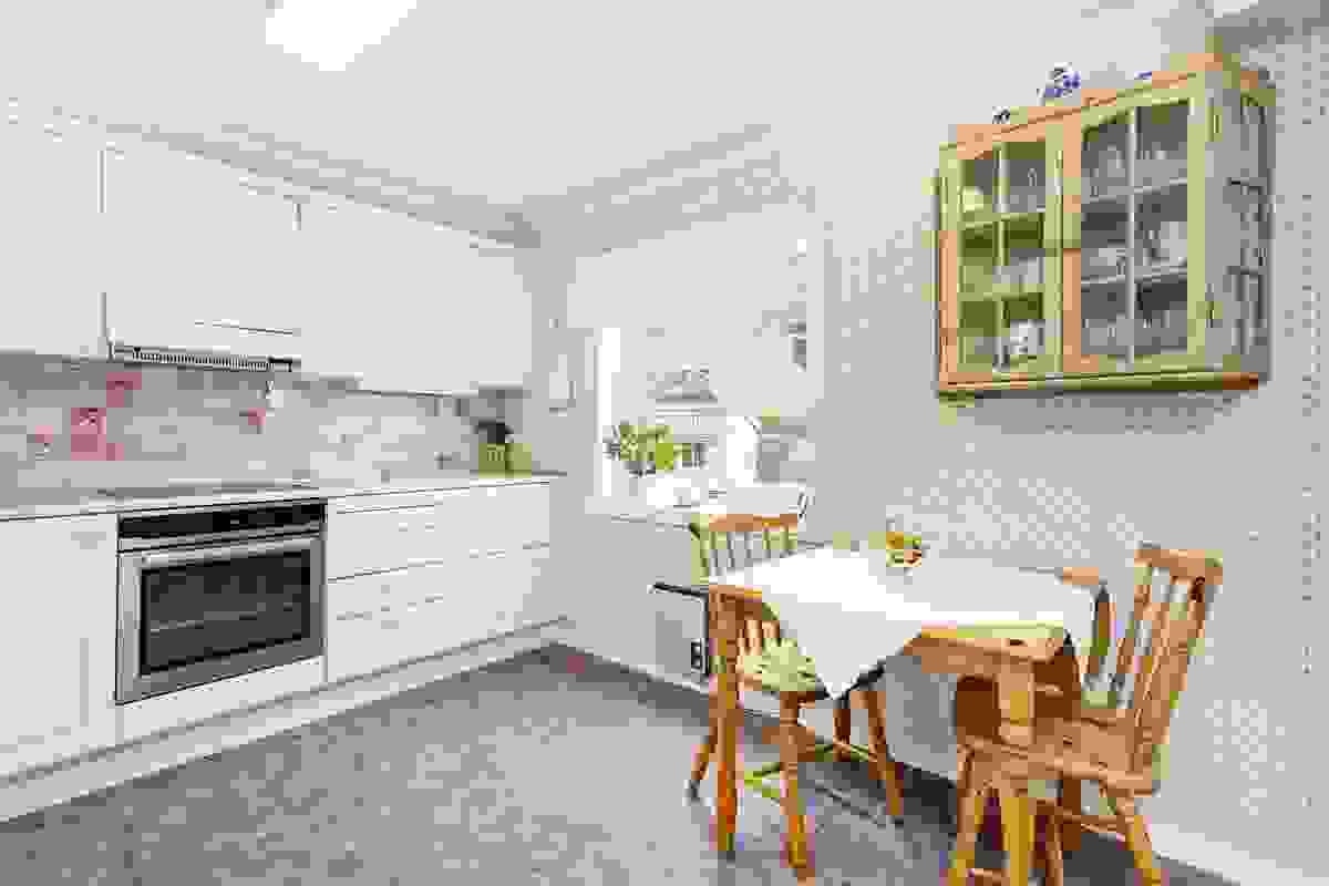 Det romslige kjøkkenet med spisesrom og utsyn mot hagen i vest