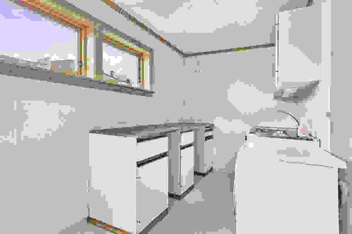 Vaskerommet fungerer med sin beliggenhet vegg-i-vegg med kjøkkenet også ypperlig som grovkjøkken