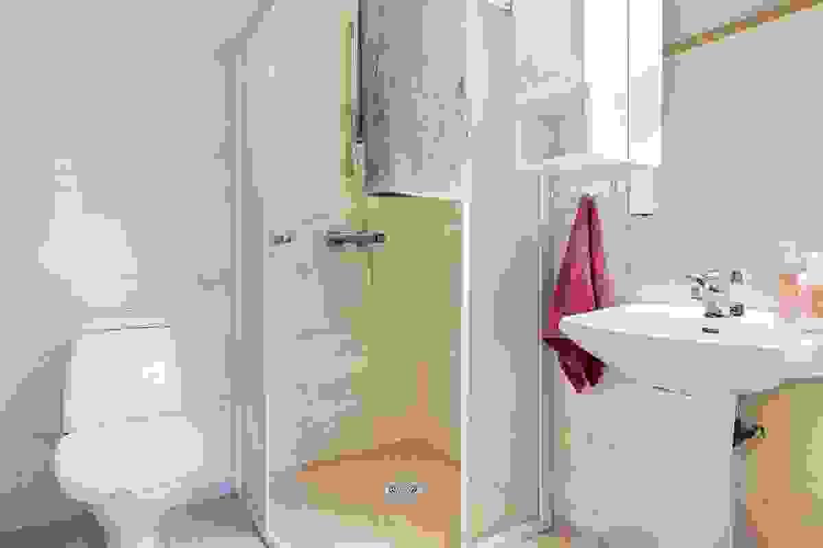 Badet i 1. etasje har enkel tilkomst fra hall/gang og er innredet med søyleservant, dusjhjørne og sokkeltoalett.