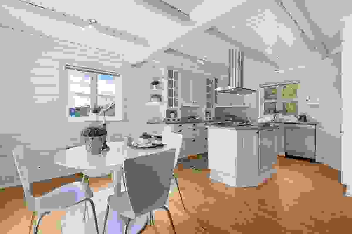 Lyst og pent kjøkken med synlige bjelker og downlights i himling