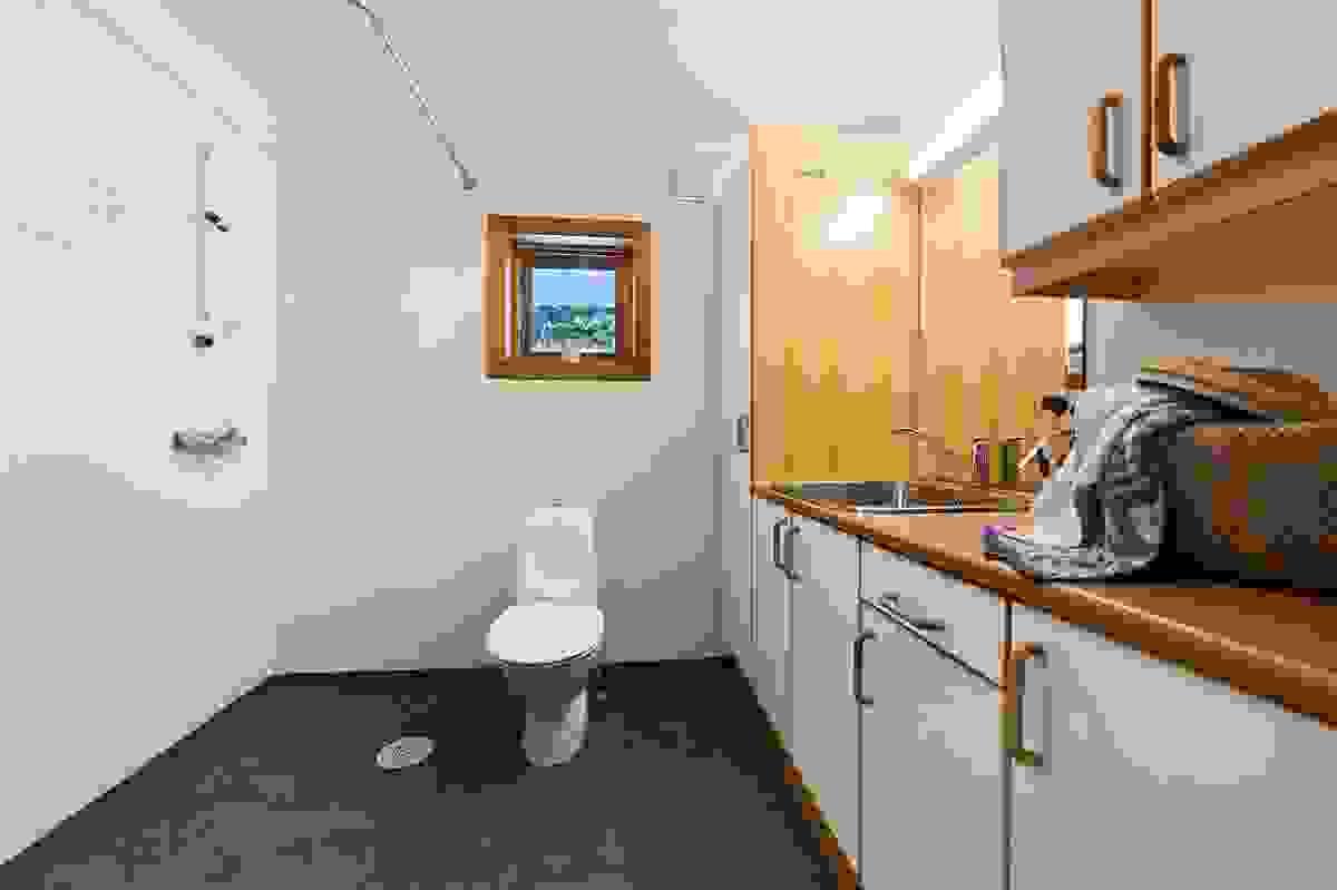 Bad/vaskerom med gulvvarme, skapinnredning med kum, dusj på vegg, WC og opplegg til vaskemaskin