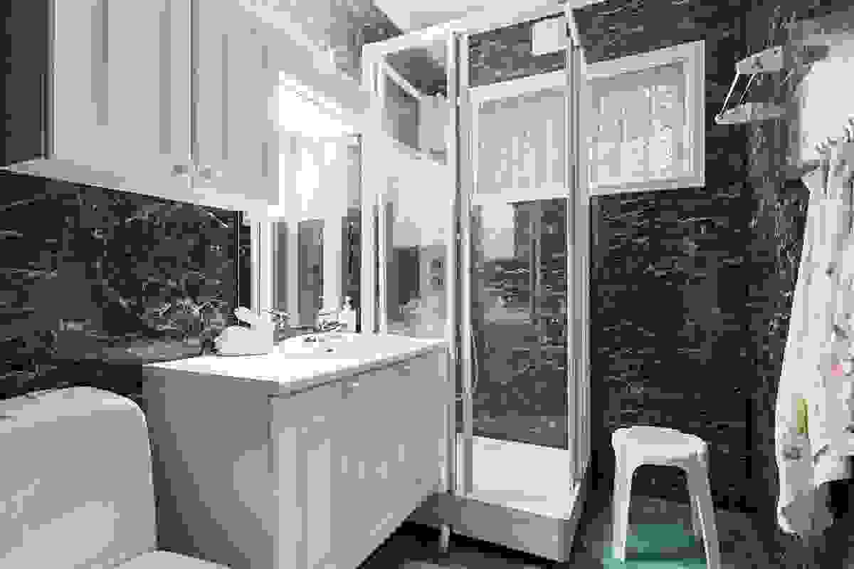Badet inneholder kabinett, servant m/skap og toalett