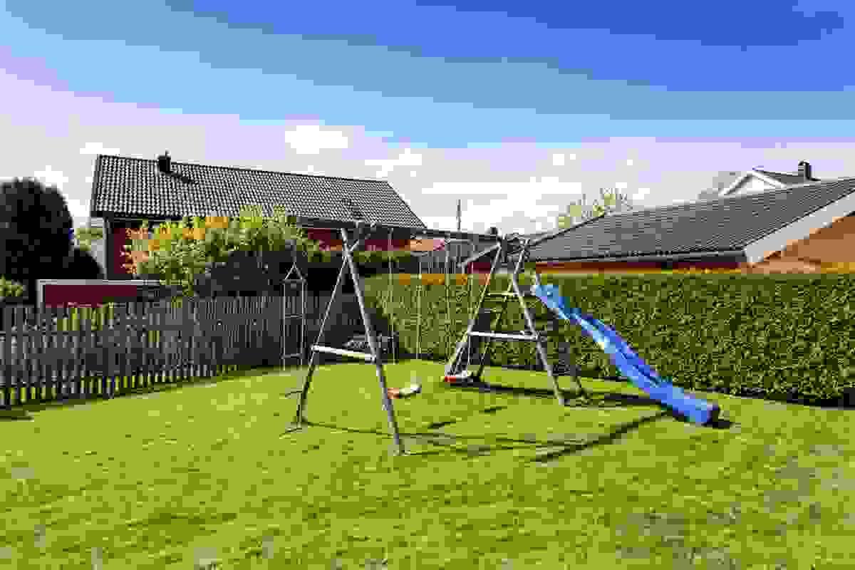 Tomten er barnevennlig og på en fin måte innhegnet av hekk, tregjerder og prydbusker