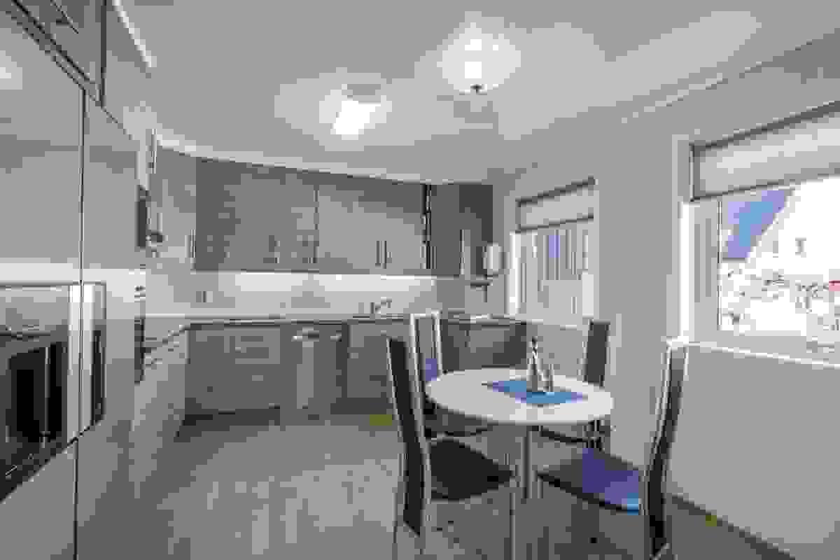 De to store vinduene ved kjøkkenets koselige spiseplass slipper inn morgenlyset til rommet